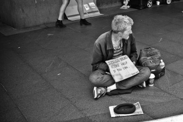 """Man begging with sign that says """"homeless and broke, please help if you can"""""""