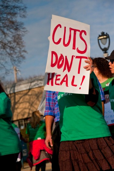 """Woman holding a sign at a demonstration. Slogan """"Cuts don't heal""""."""