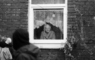 Elderly woman looking out of her window