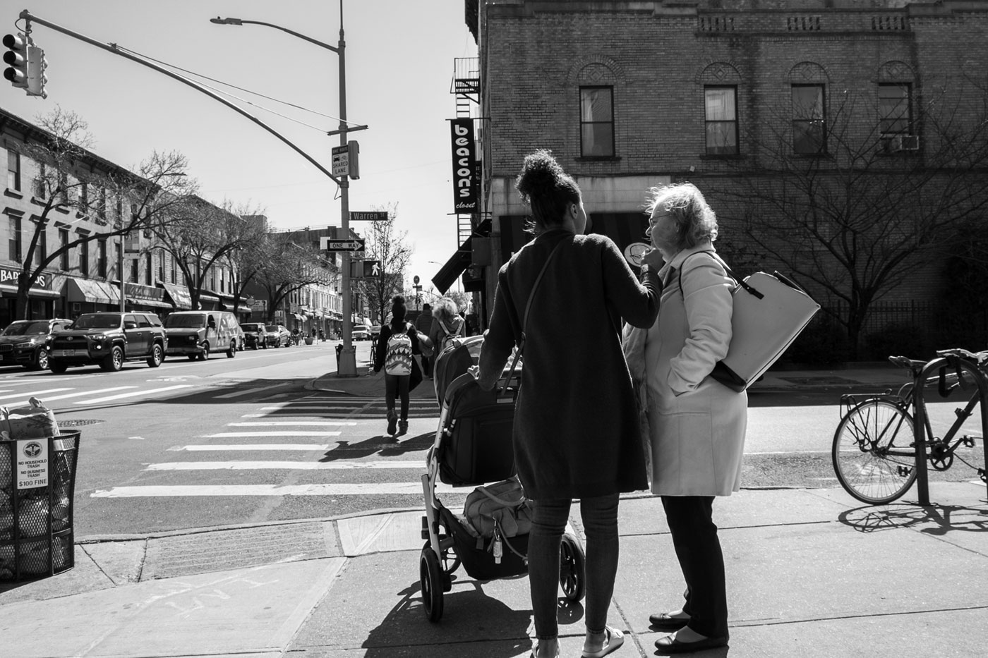 two women talking at a crosswalk