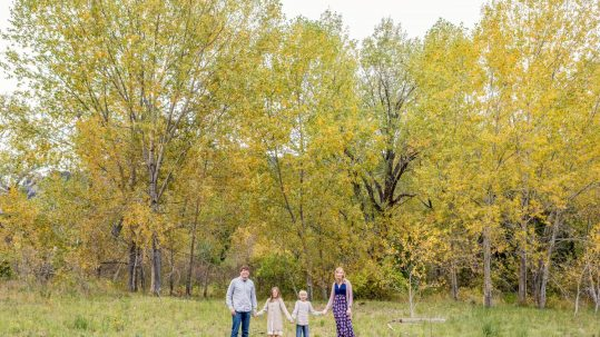 family standing in woods