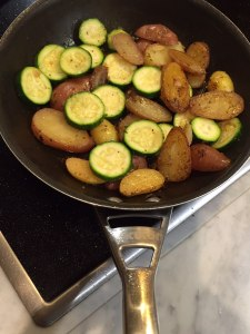 Shot showing the fondant potatoes and courgettes cooking in the pan.