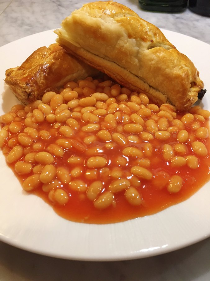 Shot showing the sauce roll served in a delicious puddle of baked beans.