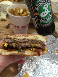 Shot showing the burger with fries and Brooklyn lager in the background.