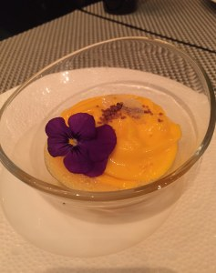 Shot showing the dramatic orange of the sorbet contrasting with the purple edible flower