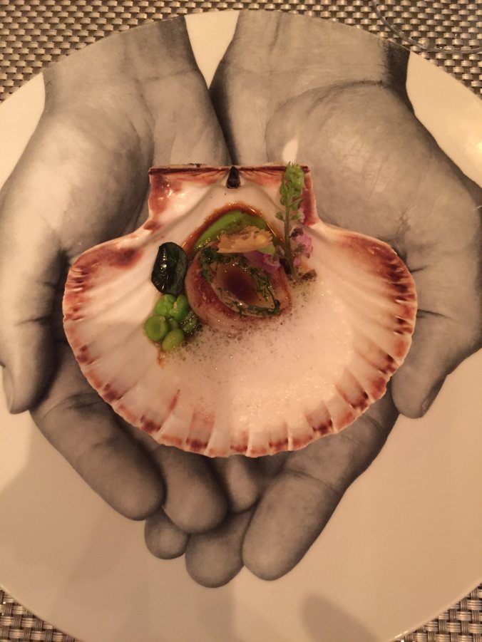 Shot of the scallop dish, presented in the shell and on a plate painted with two outstretched hands