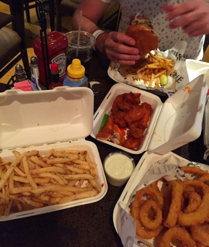 A cornucopia of drunk snacks; garlic fries, chicken wings, a burger and onion rings.