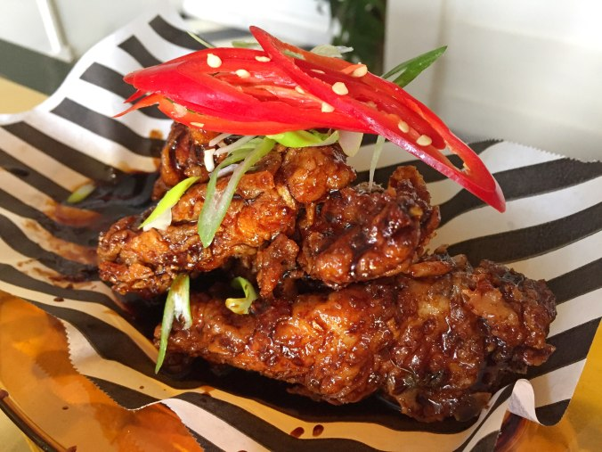 Soy and garlic chicken tenders with a glossy soy glaze, topped with shredded spring onion and sliced chilli.