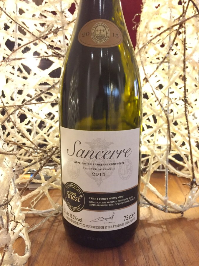 Close up shot of the bottle of Sancerre lit buy Christmas trees