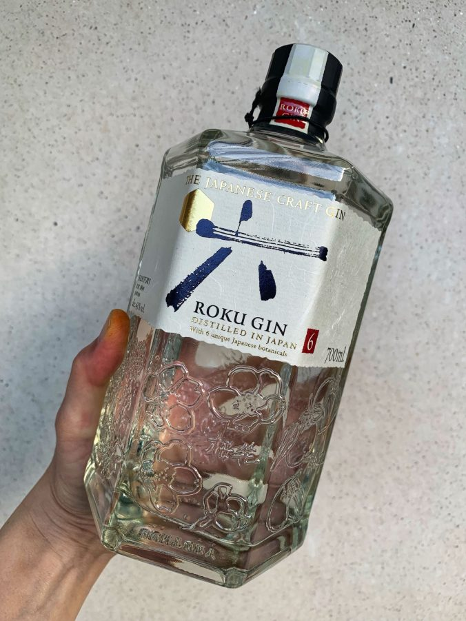 The bottle of Roku gin is clear glass and hexagonal. It has a very striking off white label with gold and black writing.