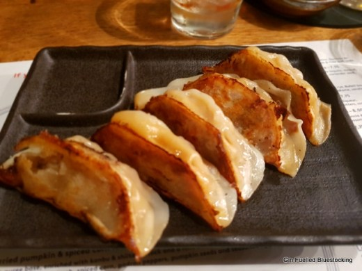 Five pan toasted gyoza dumplings sit on top of a black square plate