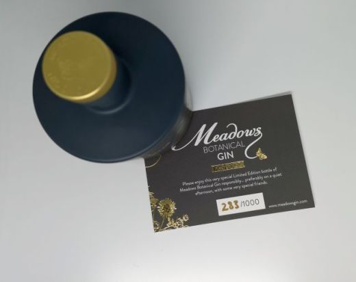 Top down shot of a grey bottle with an embossed gold cap, positioned on the corner of a rectangle of grey card, which is a batch certificate from Meadows Gin.