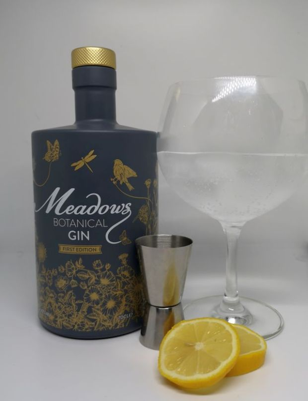 Image of a grey bottle decorated with gold flowers and birds, alongside a silver jigger, slices of lemon and a gin copa glass filled with gin tonic and ice, with a white background.