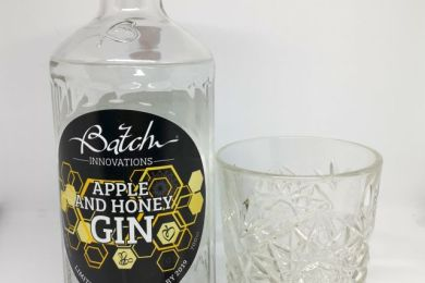 A clear glass bottle of Batch Gin, the label features a honeycome and bees, sitting next to a patterned cut glass filled with gin and a silver jigger