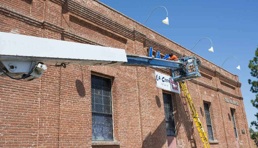small crane carrying worker to install sign on brick building