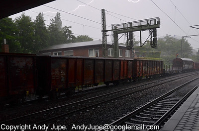 With lightning streaking across the sky and me hiding underneath the Harburg bypass, bogie box wagon Eans 31 80 5419 039-8 passes through Hamburg Harburg station, Germany on the 19th July 2012