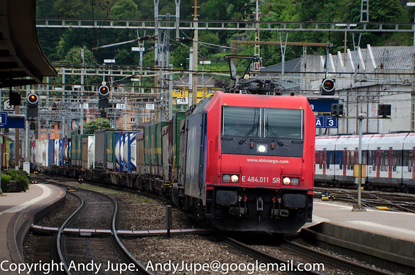 Bombardier TRAXX F140 MS, Re 484, number 484 011-2 (E 484.011 SR) sweeps South through the reverse curves and cambers at Bellinzona station in Switzerland at the head of train number 43075 Duisburg Ruhrort Hafen to Busto A/Gallarate HUPAC Intermodal service.