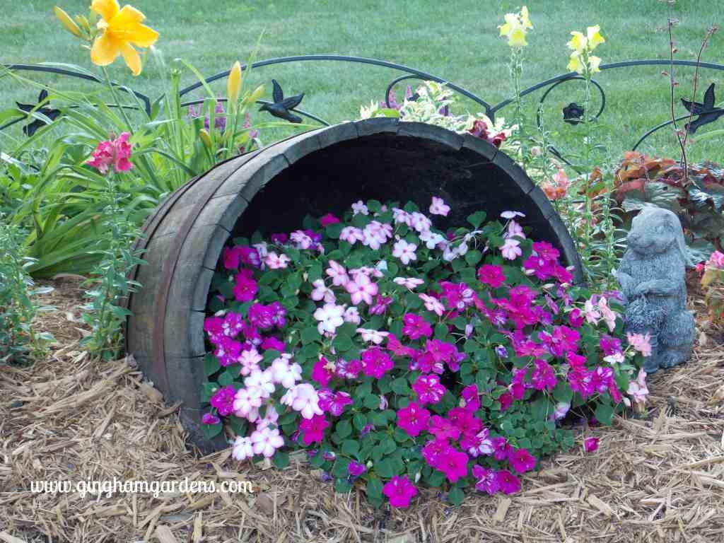 Creative Flower Container Gardening - Impatiens spilling out of a tipped wine barrel.