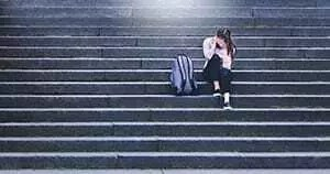 Depressed college woman crying on stairs