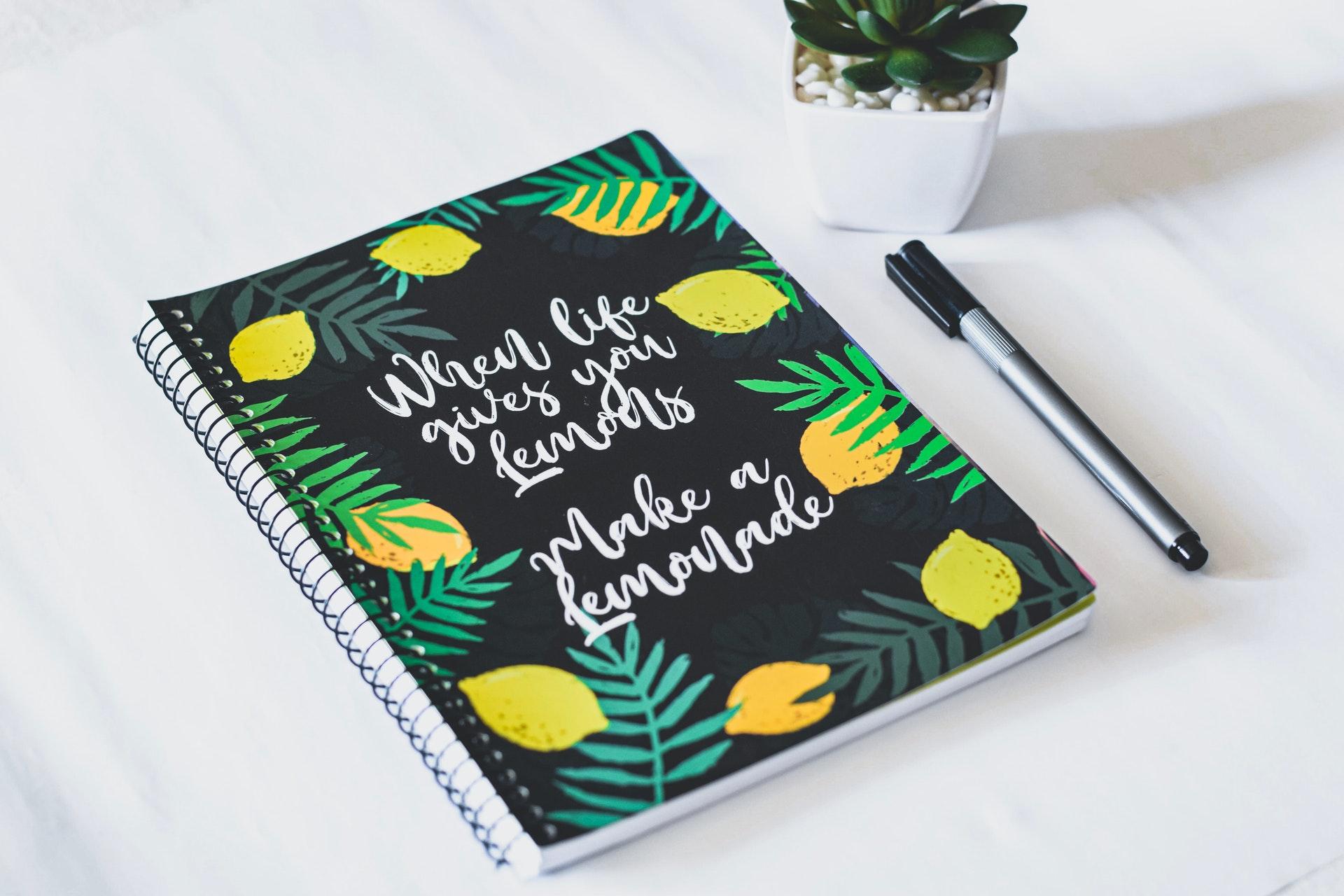 Desk with book saying when life gives you lemons make lemonade