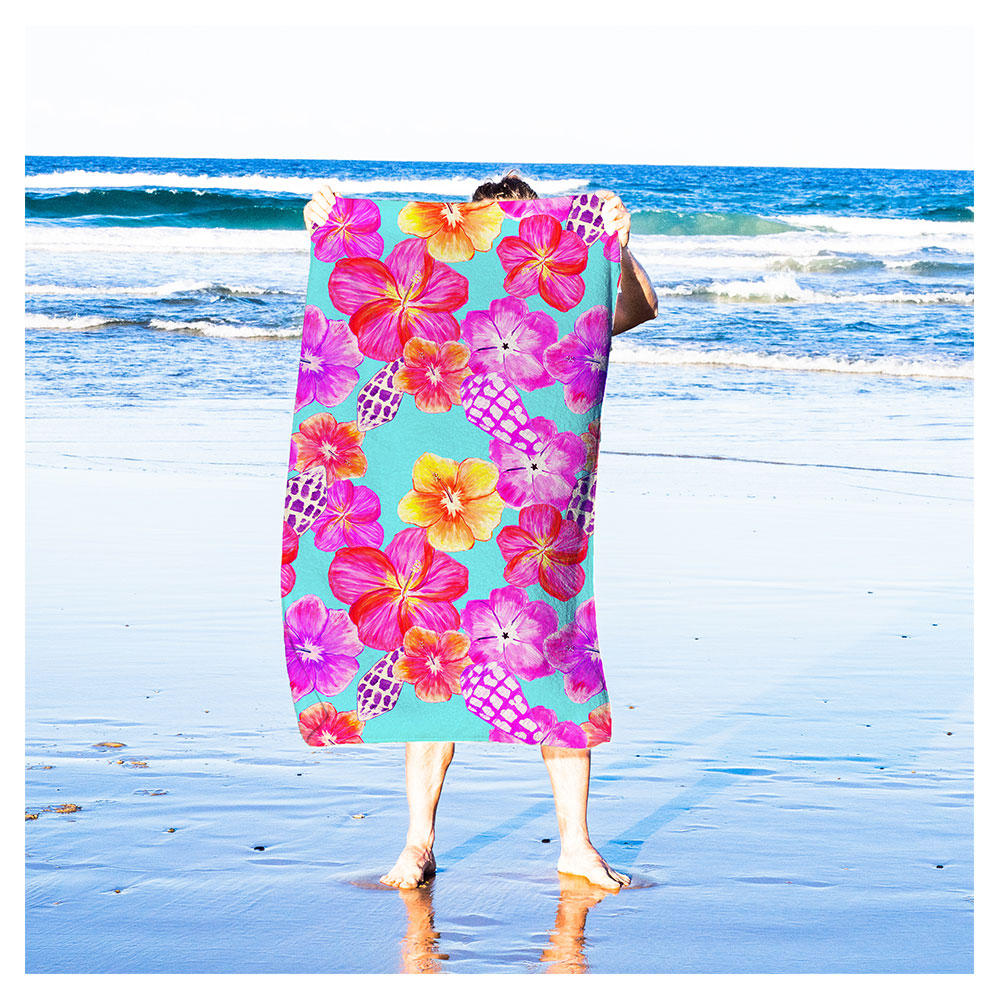 person holding beach towel with bright seamless surface pattern design of hand-painted flowers and shells
