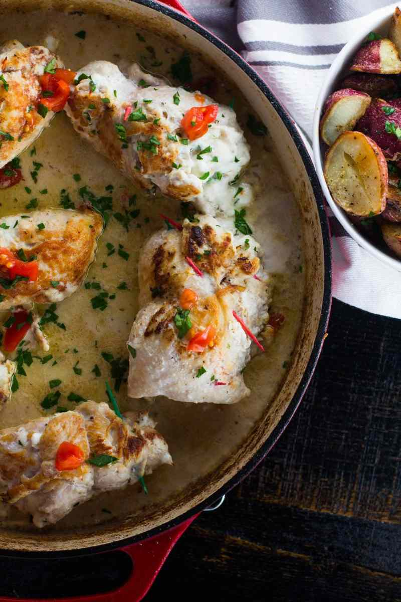 This stuffed chicken breast is loaded with silky and creamy garlic cheese and surrounded by a creamy white wine and shallot sauce. Quick, easy and the perfect mid-week meal.