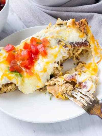 These Creamy White Chicken Enchiladas are beyond simple to make but are incredibly flavor! Slathered in a ridiculously delicious creamy sauce and covered in stretchy cheese, these enchiladas need nothing else except a fork and a knife to dive in with!