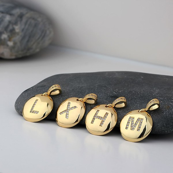 A photo showing pendants with initials, L, X, H, and M that goes with the gold necklace. The pendants are laid on a rock for the close up.