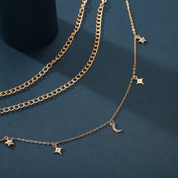Moon and Star Necklace displayed land laid out on a dark blue surface