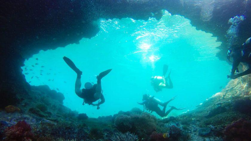 Swimming through a cave in Batu Rufus