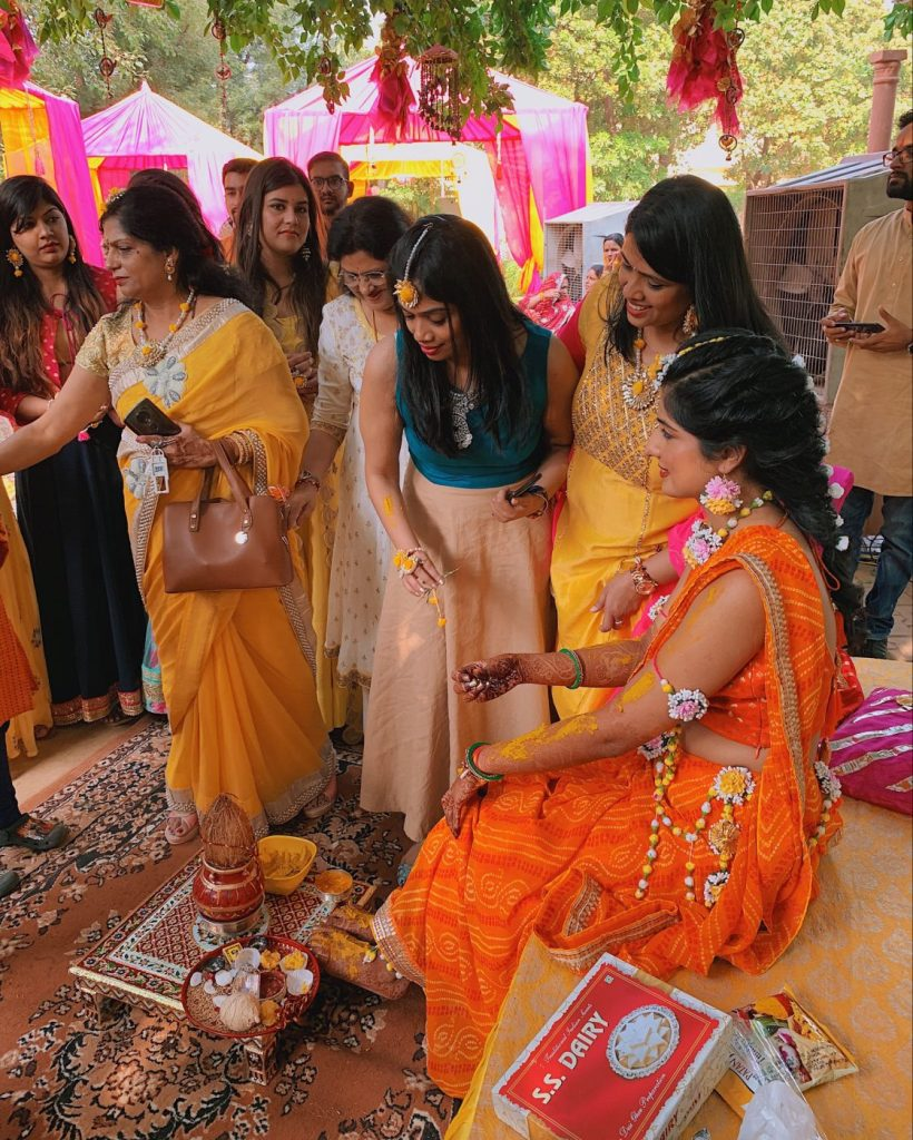 Bride getting turmeric paste on her hands