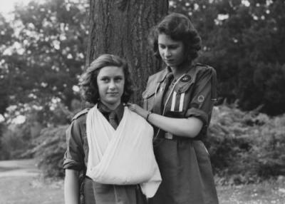 Princess Elizabeth places Princess Margaret's arm in a sling as part of the girl guides in Frogmore, Windsor, England on April 11, 1942. (Photo by Studio Lisa/Getty Images)