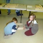 Kenzie & Lili putting starting nails in a board