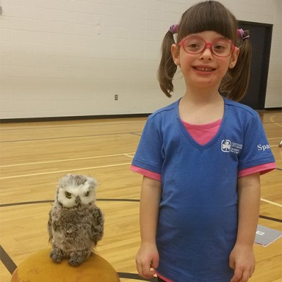 Malina, a Spark from Edmonton, Alberta in a blue Girl Guides uniform standing next to an owl.