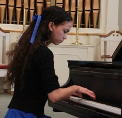 A picture of me, your teacher for online piano lessons, playing piano in my senior undergraduate recital