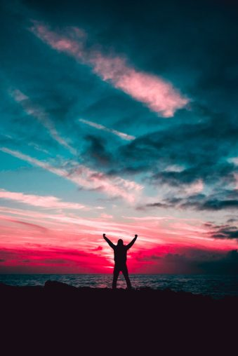 Person with arms raised as if in victory standing in front of a vibrant pink and blue sunrise or sunset over water.