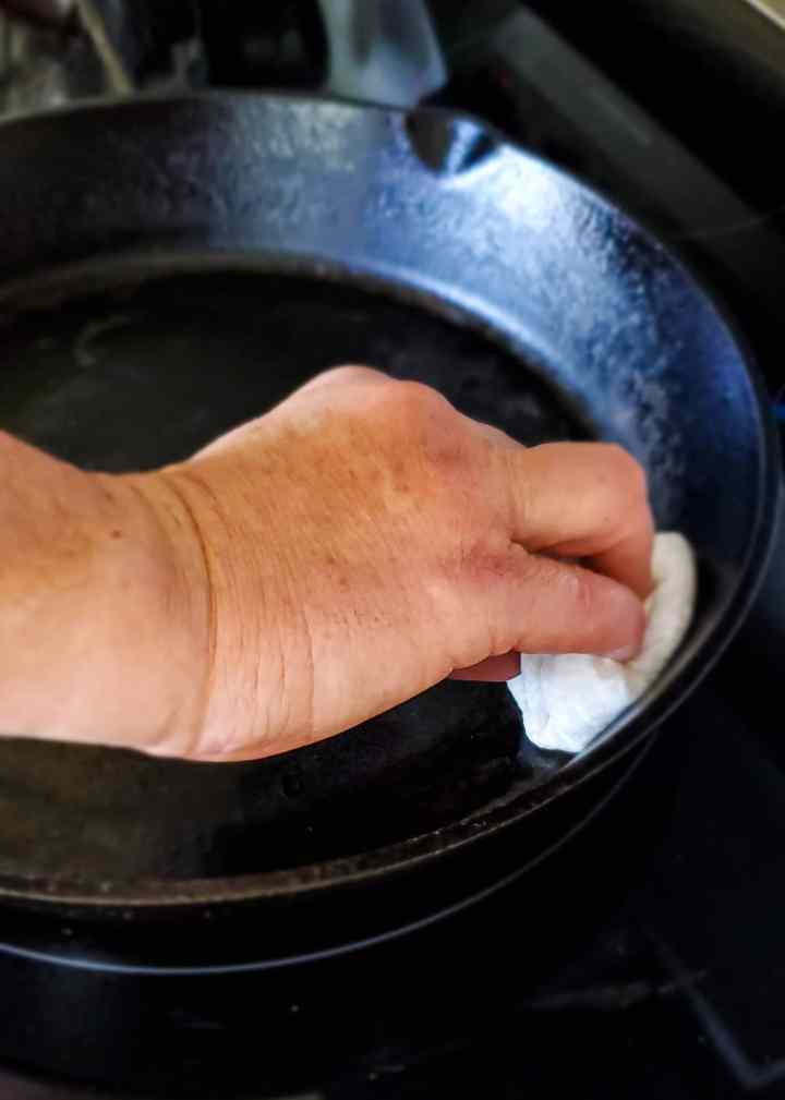 a hand rubbing the paper towel sponge with oil on to the clean cast iron skillet
