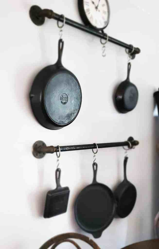 A wall with two iron pipes with hooks holding five different cast iron skillets