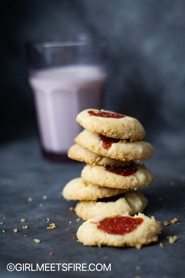 guava topped polvorones stacked up with a glass of milk on the background