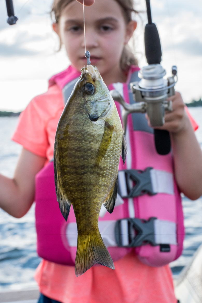Girl holding fishing rod with sunny attached to the hook