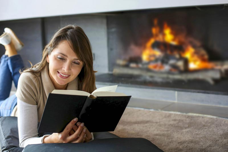 Woman reading by fire