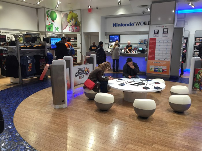 First floor at the Nintendo World Store in NYC. My sister playing Super Smash Bros. on 3DS © Leah Jewer / Girls on Games