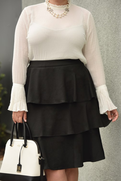 Girl With Curves blogger Tanesha Awasthi wears a plus size ruffle skirt, bell sleeve blouse, kate spade bag, Chanel necklace.