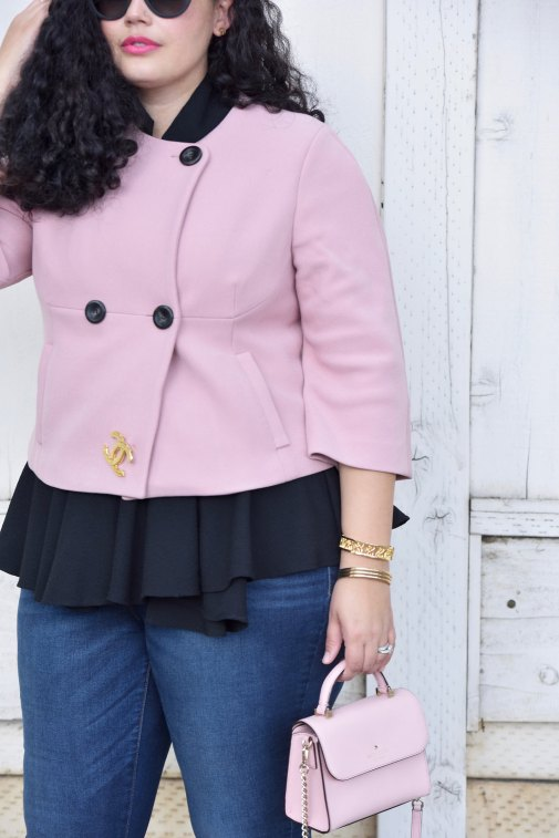 Girl With Curves blogger Tanesha Awasthi wears a pink cropped jacket, peplum top, skinny jeans and leopard flats.