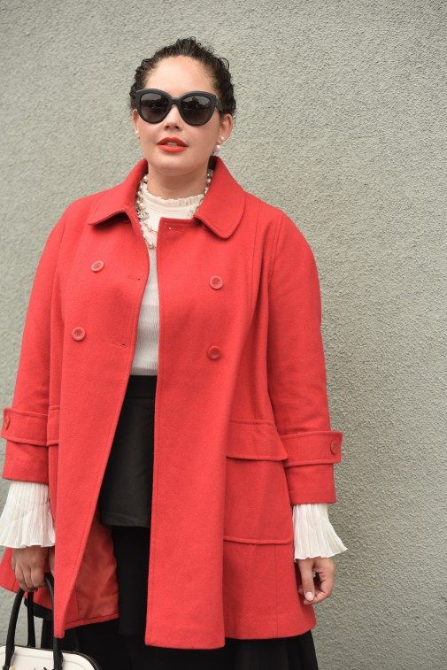 Girl With Curves blogger Tanesha Awasthi wears a plus size ruffle skirt, bell sleeve blouse, red swing coat, kate spade bag, Chanel sunglasses and Chanel necklace.