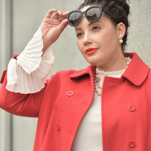 Girl With Curves blogger Tanesha Awasthi wears a bell sleeve blouse, red swing coat, kate spade bag, Chanel sunglasses and Chanel necklace.