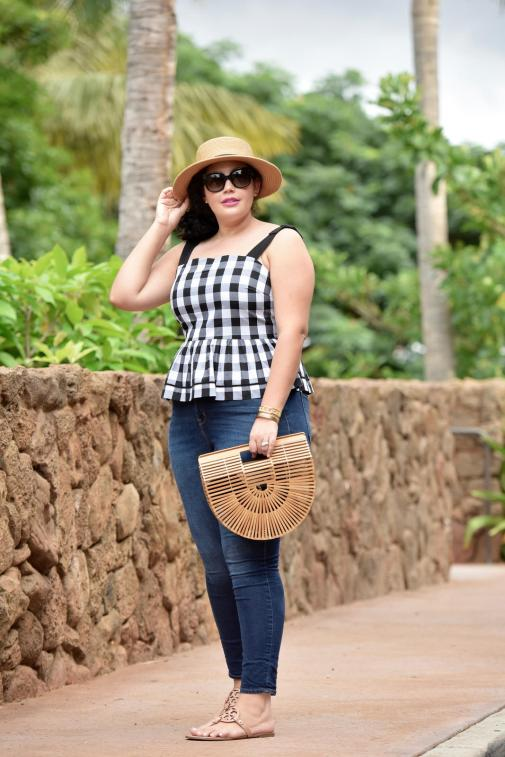 Girl With Curves blogger Tanesha Awasthi wears a gingham peplum, skinny jeans, wicker bag, Celine sunglasses, Tory Burch sandals and boater hat in Hawaii.