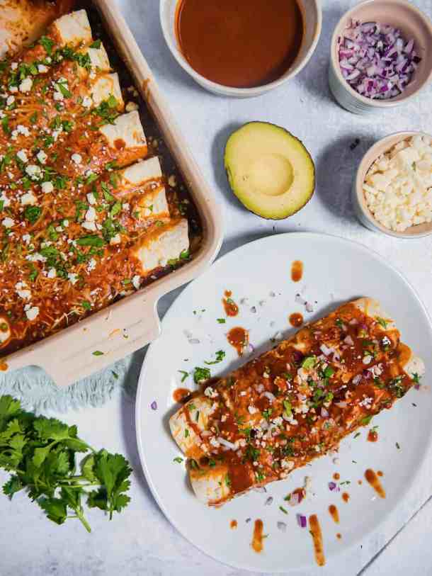 flatlay of chicken enchiladas in a baking dish, two enchiladas on a white plate, an avocado, cilantro, red onion, and jar of cotija cheese