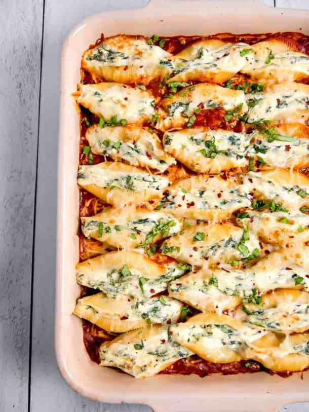 spinach and cheese stuffed shells overhead shot in a baking dish in red sauce with fresh basil