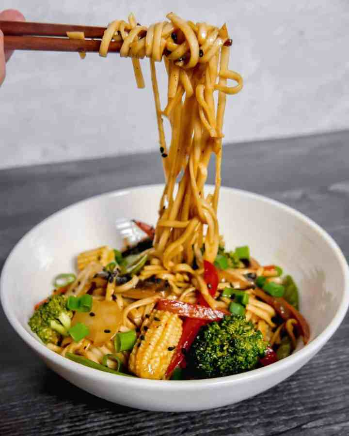 photo of vegetable lo mein noodles being pulled up from the bowl by chopsticks